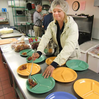 Kim Storey helping serve lunch at Crisis Nursery